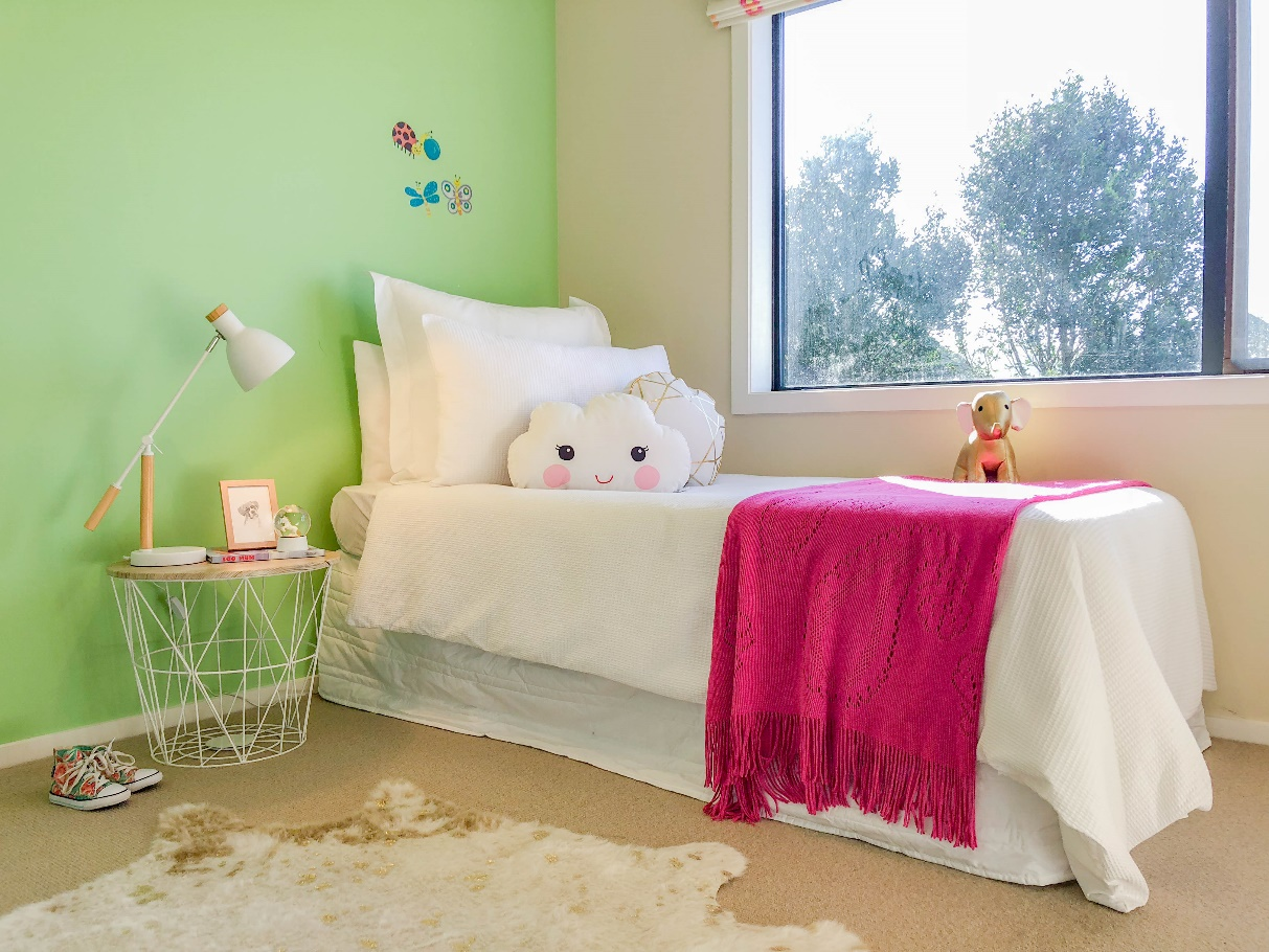 A HomeStaged kids bedroom with green walls and a white and pink bed.