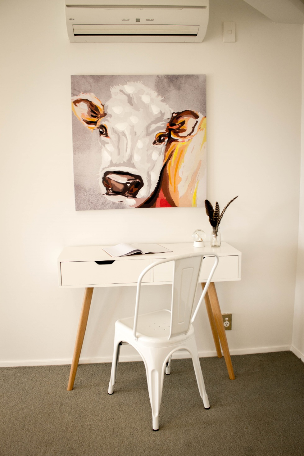 A painting of a cow in a Home Staged space