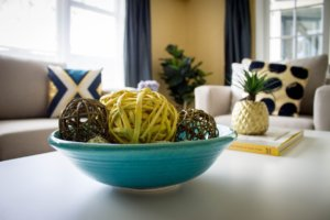 A home staged table decorated with a bowl and a plant