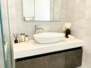 A bathroom sink staged with functional elements such as towels and cotton buds