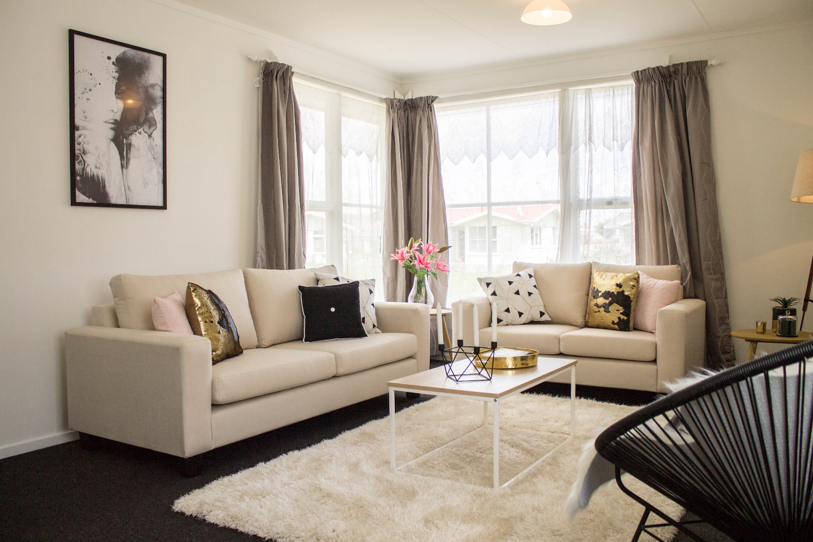 A homestaged lounge room with couches, a rug and accessories